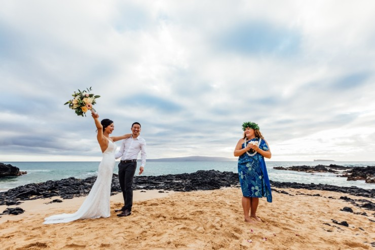 Bride and Groom on a beach with a Minister in Hawaiian style clothes